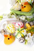 Easter eggs in green basket with chickens