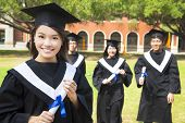 Pretty College Graduate Holds A Diploma With Classmates