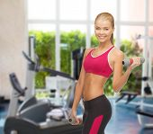 fitness and gym concept - young sporty woman with light dumbbells