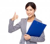 Businesswoman with clipboard and thumb up