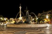 Rossio square, downtown Lisbon, at night, with fountain and Pedro IV column.