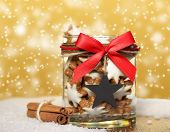 stock photo of ginger bread  - Ribbon bow tied on jar with ginger bread and cinnamon - JPG