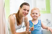 Mother With Child Boy Brushing Teeth