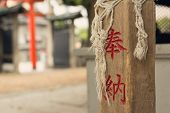 The red donated text engraved on the wooden pillar in Tenmangu in Osaka.