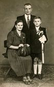 SIERADZ, POLAND, CIRCA FIFTIES - Vintage photo of parents with their son at his First Communion