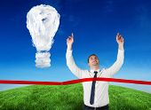 Composite image of businessman crossing finishing line against cloud light bulb