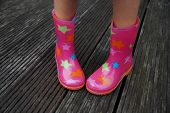 Shy child legs in rubber boots (galoshes)