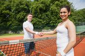 Tennis opponents shaking hands before match on a sunny day