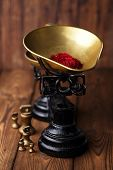 saffron spice in antique vintage iron scale bowl  on wooden table, shallow dof
