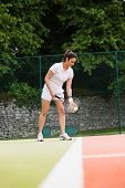 Pretty tennis player ready to serve on a sunny day