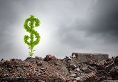 Conceptual image of green dollar sign growing on ruins