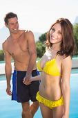 Happy romantic young couple holding hands by swimming pool on a sunny day