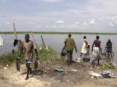 BOR, SOUTH SUDAN-JUNE 26 2012: Unidentified people go about business fishing and washing at the Nile
