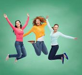 happiness, freedom, friendship, education and people concept - smiling young women jumping in air ov