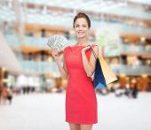 shopping, sale, gifts, money and holidays concept - smiling woman in red dress with shopping bags an