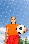 Girl holding football in one arm standing