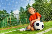Smiling girl with bending arm on football sitting