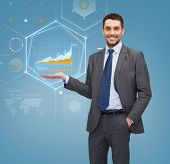 business, office, advertising and people concept - businessman showing virtual screen with graphs