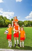 stock photo of pyramid shape  - Happy kids with won cup stand in pyramid shape together - JPG