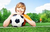 Boy holds football with bending in elbows arms