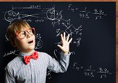 Smart boy in red glasses near blackboard with formulas