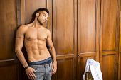 stock photo of undressing  - Sexy handsome young man standing shirtless in his bedroom with a shirt draped over chair with a smile - JPG