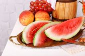 Composition of ripe watermelon, fruits, pink wine in glass and wooden barrel on  color wooden table,