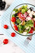 Glass bowl of Greek salad served on napkin on wooden background