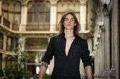 Handsome Long Hair Young Man Indoors In Elegant Gallery