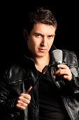 Male singer holding a microphone on black background