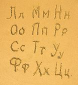 Russian alphabet (2/3) written on a sand beach. (series of three parts)
