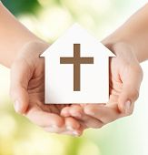 religion, christianity and charity concept - close up of woman hands holding paper house with christian cross symbol over green background