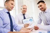 business, office and people concept - smiling businessmen with papers in office