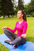sport, meditation, park and lifestyle concept - smiling african american woman meditating on mat outdoors
