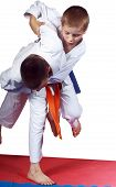 Active athletes in  judogi are performing throws
