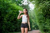Woman Athlete Takes A Break. Drinking Water, Out On A Run In The Park