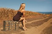 Sexy blonde woman sits on an old suitcase outdoors