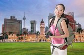 Happy smiling Asian young female backpacker with camera standing in front of skyscrapers in Kuala Lumpur, Malaysia.
