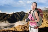 Happy smiling Asian young female backpacker with camera standing in front of mountains.