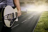 Постер, плакат: Guitarist And His Guitar On The Road