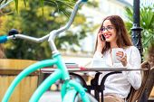 Young Woman Sitting In The Open Air Cafe With Cup Of Coffee And Bicycle And Speaking Phone In The Mo