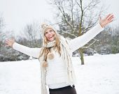 Happy woman standing in winter snow with her arms stretched out