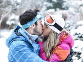 Happy couple kissing in winter on a ski trip in the snow