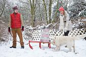 Couple with christmas gifts on sled in winter with dog
