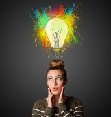 Pretty young woman gesturing with lightbulb and paint splashes above her head