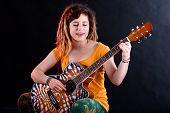 Teenage Girl Singing And Playing Guitar