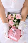 Bride in gloves holding wedding bouquet, close-up