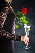 a young woman in evening dress with a red rose and a glass of sparkling wine or champagne. symbolic
