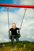 pic of swingset  - Little blonde boy having fun at the playground - JPG
