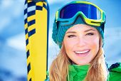 Closeup portrait of cheerful smiling girl wearing sportive equipment, active female enjoying ski sport, happy winter vacation concept